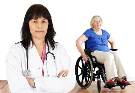 the elderly residence: Friendly woman doctor looking at camera with handicap senior in wheelchair in the back