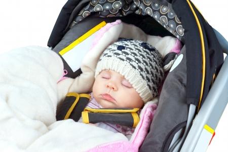 Cute Neugeborenen Mädchen schläft im Autositz, Winterkleidung