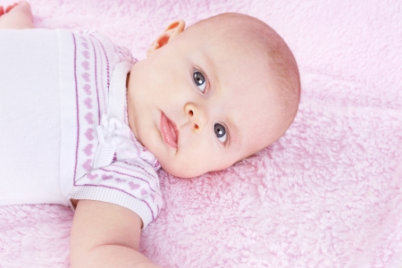 Portrait of newborn baby girl looking at camera, laying on pink blanket photo