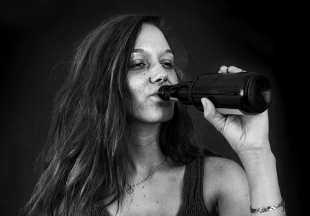 Dramatic black and white portrait of drunk young woman drinking beer over black photo
