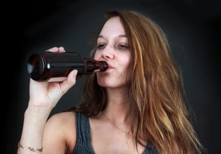 binge: Portrait of drunk young woman drinking beer over black Stock Photo