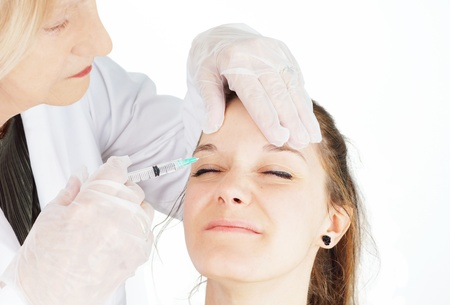 Beautiful young woman getting botox injection to remove wrinkles