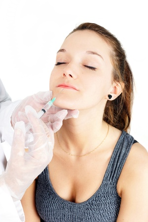 Beautiful young woman getting lip injection, botox or collagen