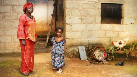 poor woman: Black African little girl and her mother in traditional clothing at home