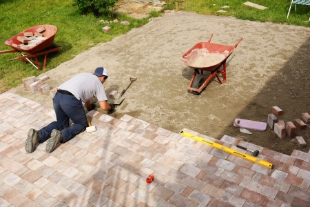 Young man installing paver bricks for large patio