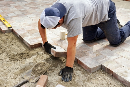 paving stone: Worker installer paver bricks on large patio