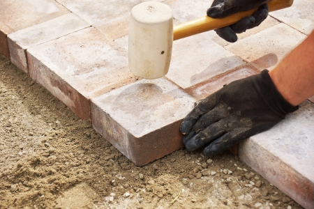 set in stone: Installing paver bricks on patio, mallet to level the stones Stock Photo