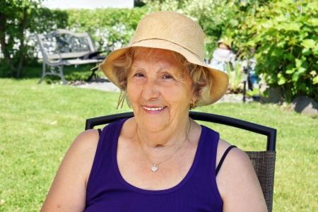 chapeau de paille: Senior femme avec un chapeau de paille à l'ombre, bénéficiant d'été