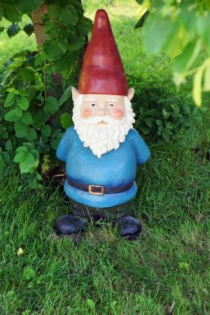Big garden gnome underneath a tree