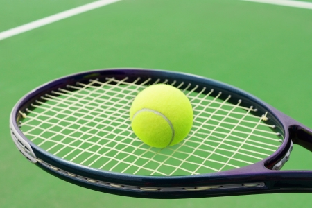 Tennis racket with ball on hard surface court photo