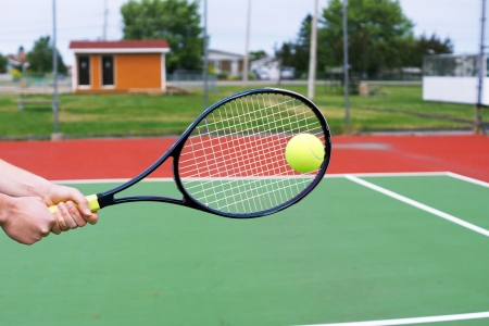 Player hands on tennis racket hitting a back hand volley photo