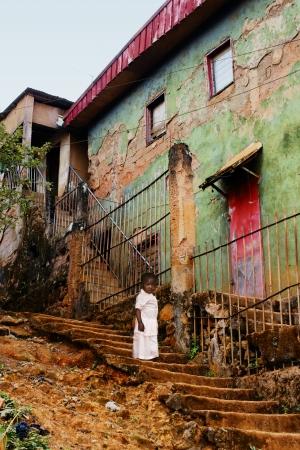 階段の古い都市の不気味なコンクリートの建物で、アフリカの少女幼児: 貧困概念。