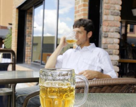 hombre tomando cerveza: Joven bebiendo cerveza, se centran en el frente de vidrio bock