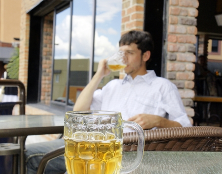 Young man drinking beer, focus on front glass bock photo