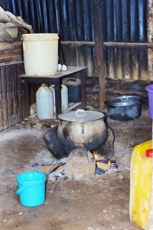 Typical African kitchen, cooking food over wood and charcoal fire photo