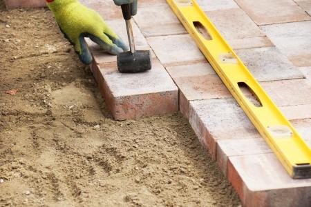 Betonmolenbakstenen installeren op terras, houten hamer om de stenen te nivelleren