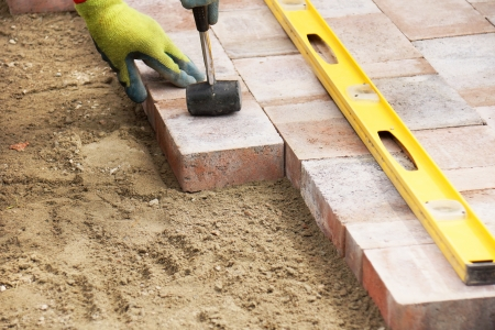 Installing paver bricks on patio, mallet to level the stones Stockfoto