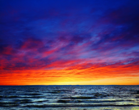 Beautiful colorful sunset over wavy waters, sea or ocean photo