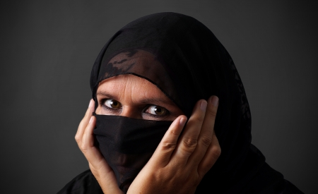 Middle-aged muslim woman hiding her face looking angry photo