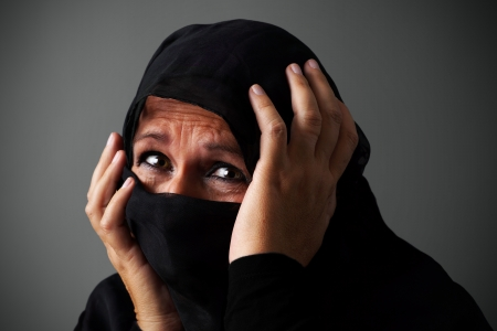 hidden danger: Muslim middle aged woman wearing the niqab in distress