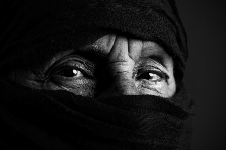 Eyes of senior muslim woman with niqab, looking at camera, black and white photo