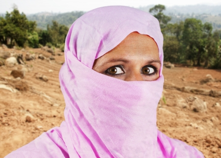 Portrait of serious middle aged muslim woman with pink scarf or hijab photo
