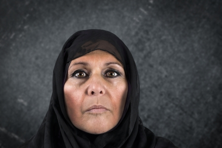 Dramatic portrait of serious middle aged muslim woman with black scarf or hijab photo