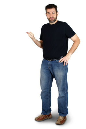 Complete body of ordinary guy or man pointing besie him and smiling, copy space