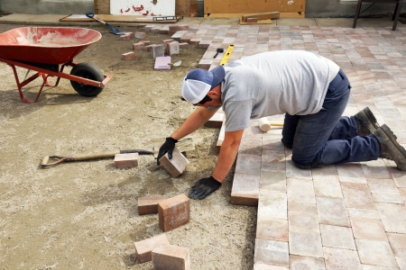 Young man laying down paver as part of landscaping