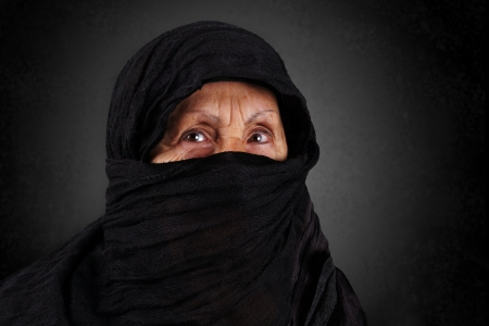 Dramatic portrait of senior muslim woman with niqab and hijab photo
