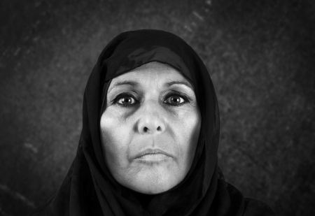 Dramatic blackand white portrait of serious middle aged muslim woman with black scarf or hijab photo