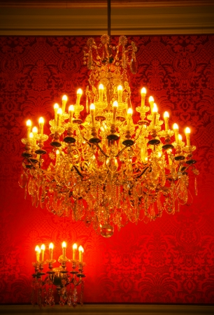 sconce: Real lavish crystal chandelier of French castle with tapestry and gold trim Stock Photo