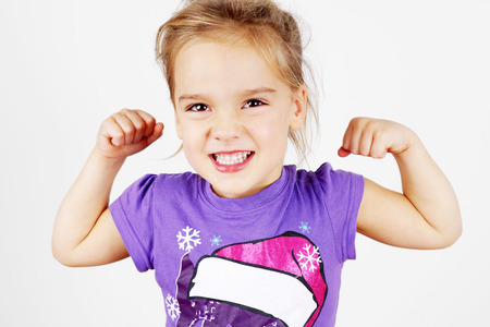 Cute and funny little blond girl showing her muscle Stock Photo - 23574630
