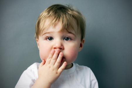 おっと!かわいいし、面白い少しの金髪の少年や幼児の口の前に手で 写真素材