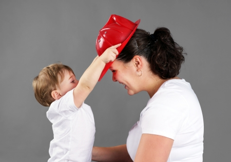 Mother and child playing, little blond boy or toddler putting a red plastic firemans hat on mom photo