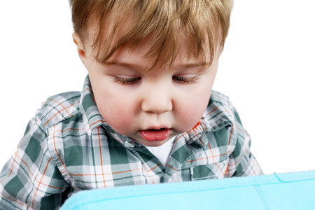 discovery: Cute little blond toddler boy looking into a blue box for discovery, growth or child development concept