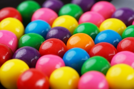 Standing out concept: focus on the only orange gumball amongst the colorful bubble gums Stockfoto