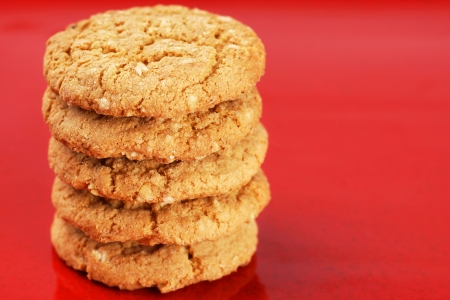 Stack of homemade peanut butter and oatmeal cookies on red enamel background 免版税图像