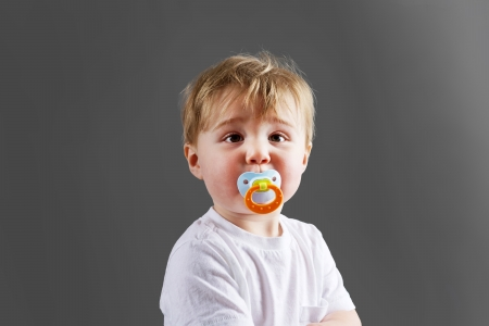 soother: Cute little blond baby boy or toddler with pacifier Stock Photo