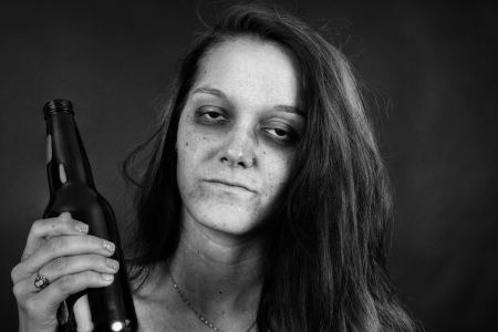 Dramatic black and white portrait of a young woman addict with beer, junkie, alcohol or drug addiction.
