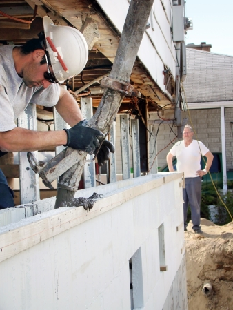 Construction or reno: Man pouring concrete in recycled blocks to make foundation under lifted house photo