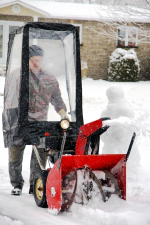 Man using snowblower in his home entryway during a winter blizzard photo