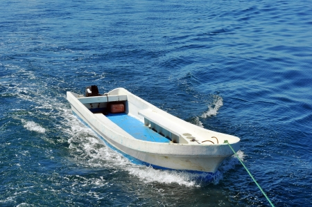 towed: Small boat being towed on the blue tropical sea Stock Photo