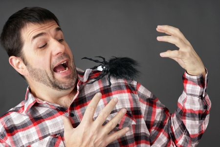 Prank or arachnaphobia concept: man scared by fake plastic spider on shoulder Фото со стока