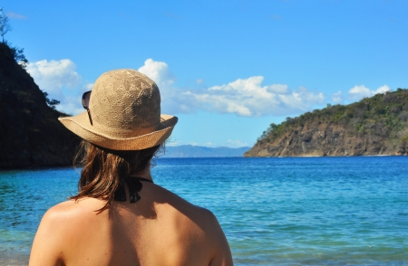 serenety: Young womans back, looking at the sea at the beach in Costa Rica