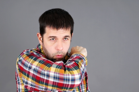 the sleeve: Sick man with a cold or flu coughing in his sleeve or elbow Stock Photo
