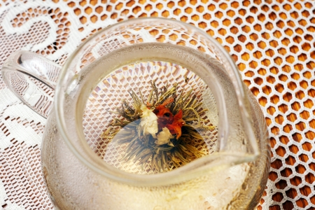 Blossom tea opening in tea pot with boiling water photo