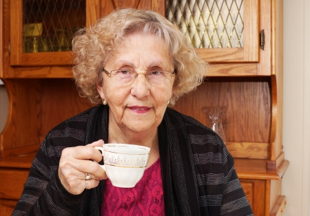 Happy senior woman drinking tea at home photo