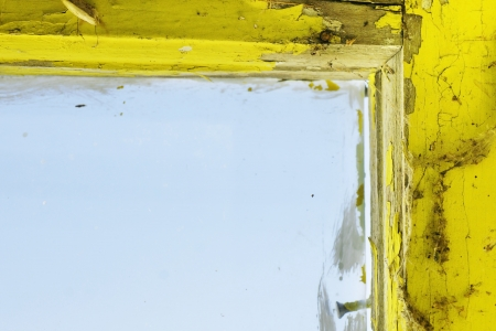 window pane: Old and dirty yellow painted wooden window frame and glass, with cobweb Stock Photo