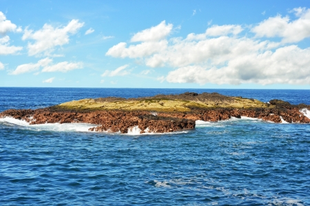 Flat lava rock formation just out of the Pacific ocean photo